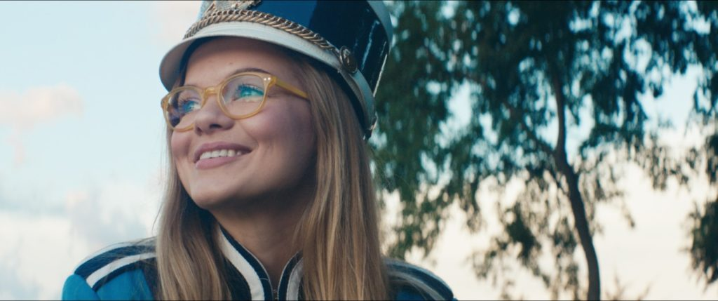 A teenage girl wearing a marching band uniform smiles and looks into the distance