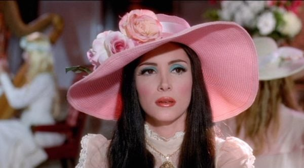 still from the Love Witch featuring a woman wearing a pink hat