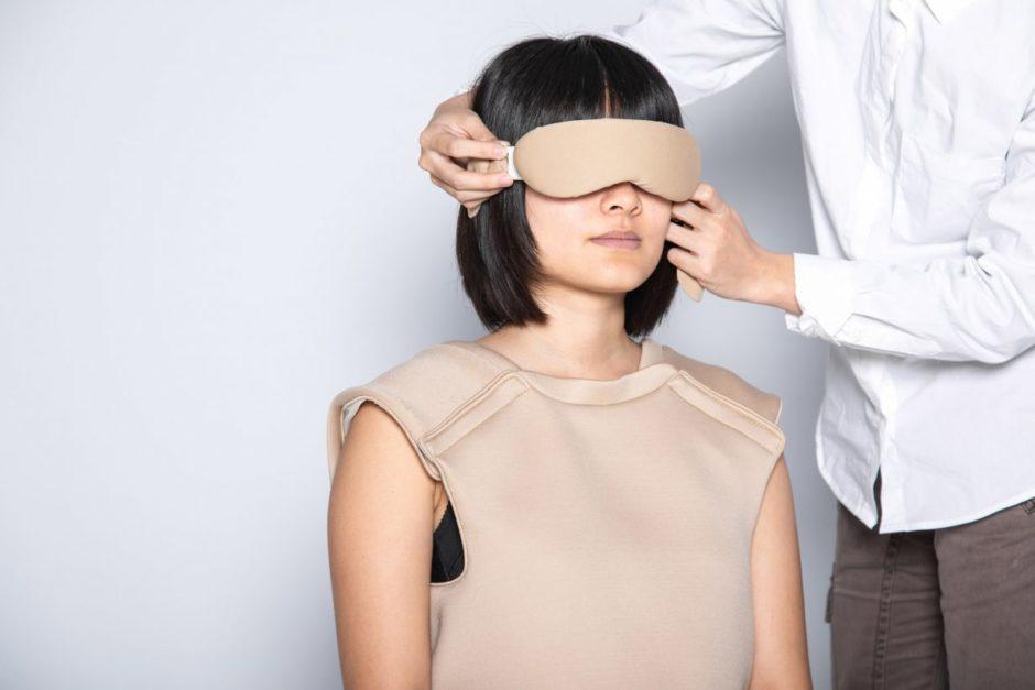 Woman wearing beige Ripple suit, blindfolded.
